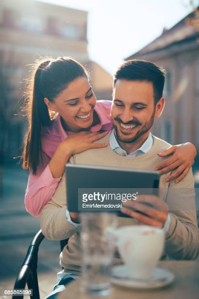 Young affectionate couple using digital tablet in cafe