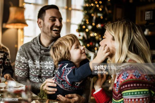 young affectionate family enjoying during new year's day in dining room. - new year's day stock pictures, royalty-free photos & images
