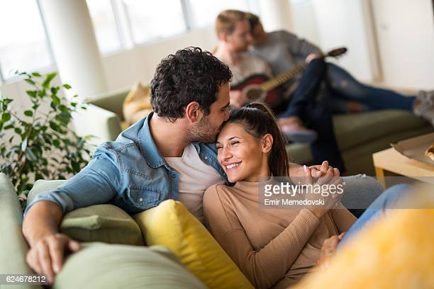 Young affectionate heterosexual couple resting on sofa and flirting