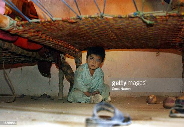 Young Afghan boy hides under a bed in his family's home during a sweep by soldiers from the U.S. Army 82nd Airborne Division November 2, 2002 in the...