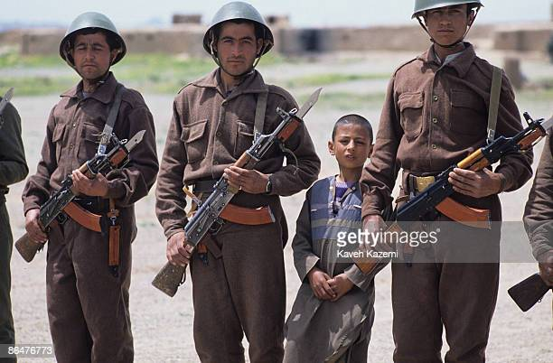 A young Afghan boy stands with a group of soldiers armed with AK47 automatic assault rifles during a reunification rally between the Mujahedin...