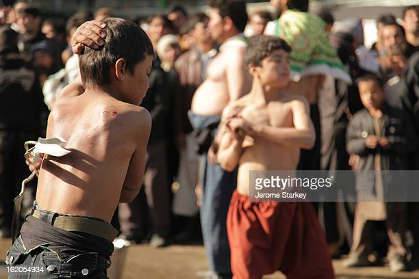 Young Afghan boys draw blood on their backs by whipping themselves with blades to mark the Shia festival of Ashura, on the tenth day of Moharram,in...