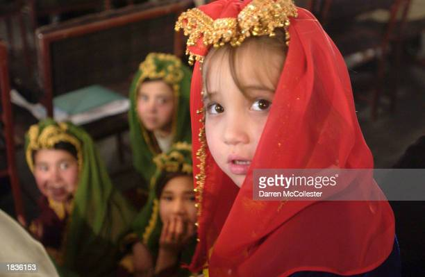A young Afghan child waits to perform a dance as she and others attend festivities for International Woman's Day March 8 2003 in Kabul Afghanistan In...