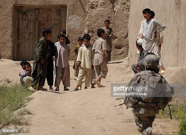 Young afghan children look on as a US soldier from the 1st Platoon Alpha 371 Cavalry secures the area during a mission at a village in the Baraki...