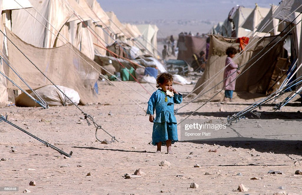 A young Afghan girl eats a piece of bread at the Chaman refugee camp November 8, 2001 on the Pakistan border with Afghanistan. The UNHCR has estimated that since September 11, 2001 over 135,000 Afghans have crossed the border into Pakistan, adding to the already millions of refugees living in the country.