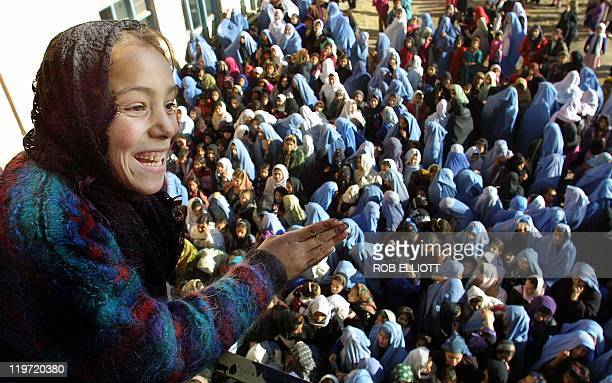 A young Afghan girl gestures to friends as she stands on a balcony above other students who have enrolled in the Sarghuna Girl's School in Kabul 30...