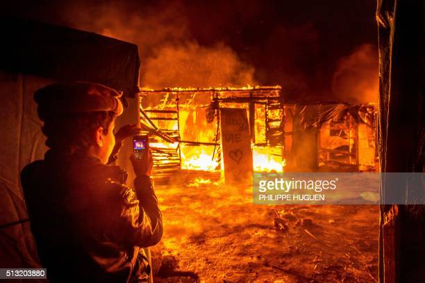 TOPSHOT A young Afghan migrant films with his phone a fire burning shacks and a placard reading 'living space' in the southern part of the socalled...