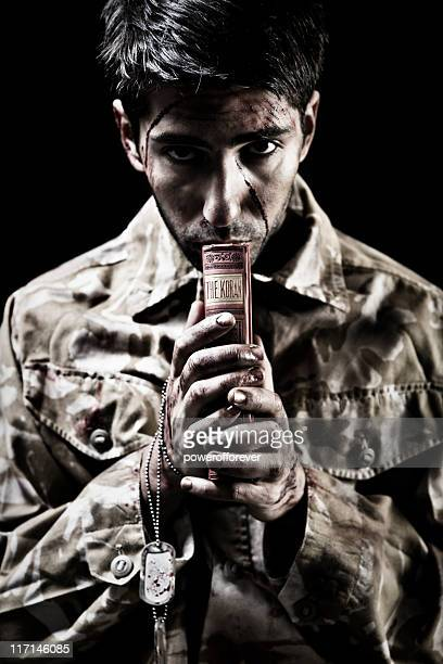 young afghan soldier clutching koran - soldier praying stock pictures, royalty-free photos & images