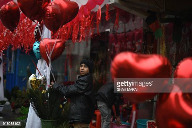 A young Afghan vendor holds heartshaped balloons as he decorates the area around a shop with flowers to be sold to celebrate Valentine's Day in Kabul...