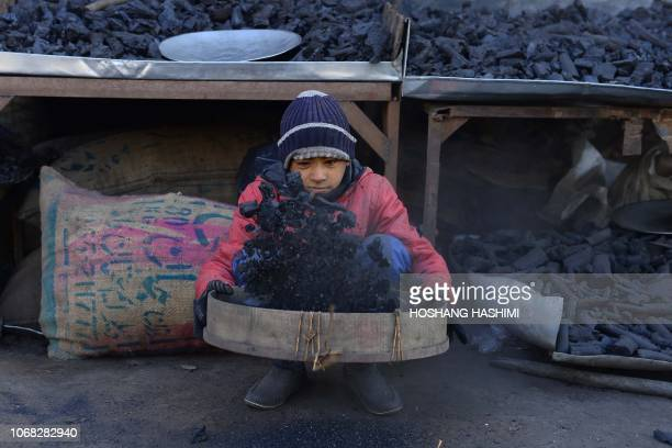 TOPSHOT A young Afghan vendor sifts charcoal at his stall in Herat city on December 4 2018