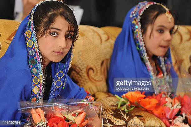 Young Afghan women in traditional clothing participate in a teachers graduation ceremony attended by Afghan President Hamid Karzai in Kabul on March...