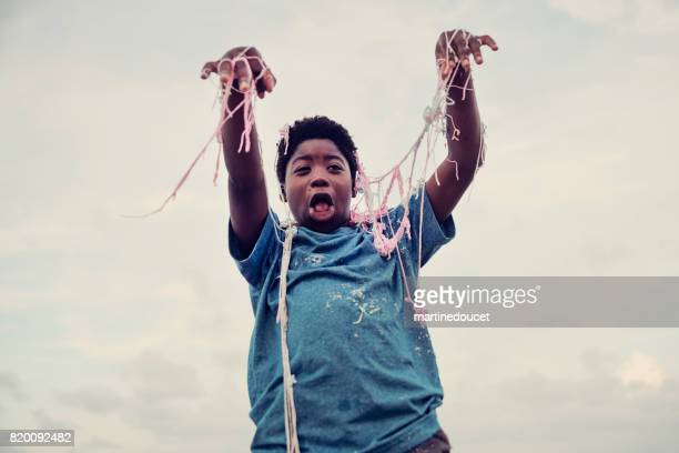 Young african american boy being string sprayed on the beach.
