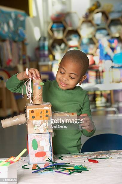 Young African American boy making art project