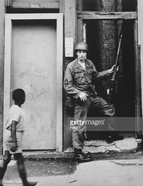 Young African American boy passes a National Guardsman in an alley of Springfield Avenue during a period of rioting in Newark, New Jersey, July 1967.