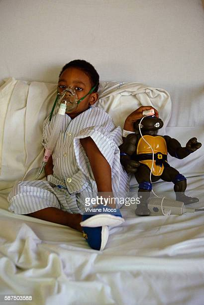 Young African American boy sits in a hospital bed with his Teenage Mutant Ninja Turtle doll as he's being treated for respiratory problems