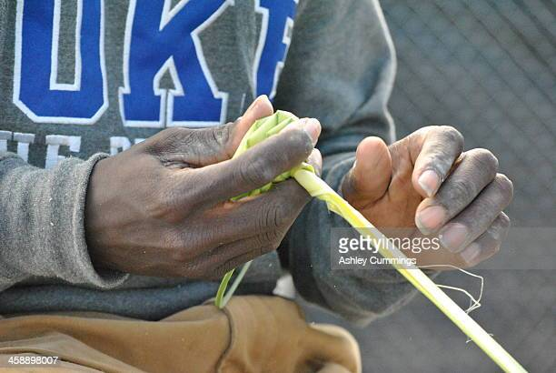 Young African American boy,continues a tradition taught to him by his grandmother, makes a palm rose from Palmetto Tree branches to sell to the...