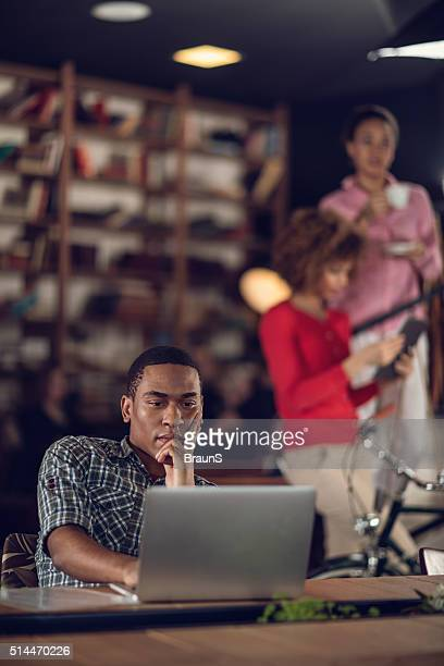 young african american businessman thinking of something while using laptop. - incidental people stock pictures, royalty-free photos & images
