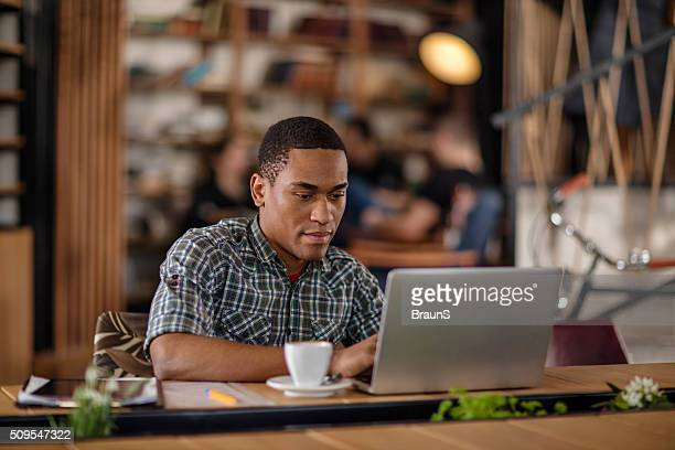 Young African American businessman working on a laptop.