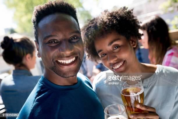 Jeune couple afro-américain en regardant la caméra en souriant tout en dégustant une bière dans un bar