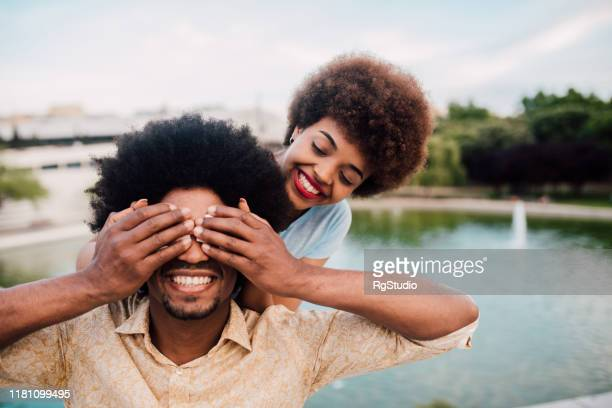 young african - american couple on a romantic vacation - hands covering eyes stock pictures, royalty-free photos & images