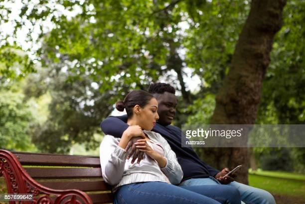 young african american couple sitting on the park bench - battersea park stock photos and pictures