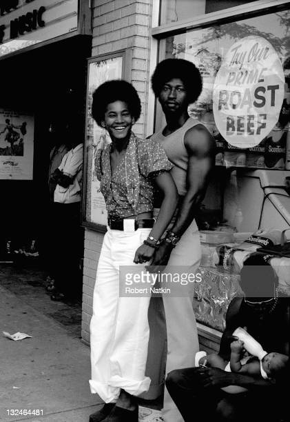 A young African American couple stand on a sidewalk in front of a grocery store with a window advertisement that reads 'Try Our Prime Roast Beef' in...
