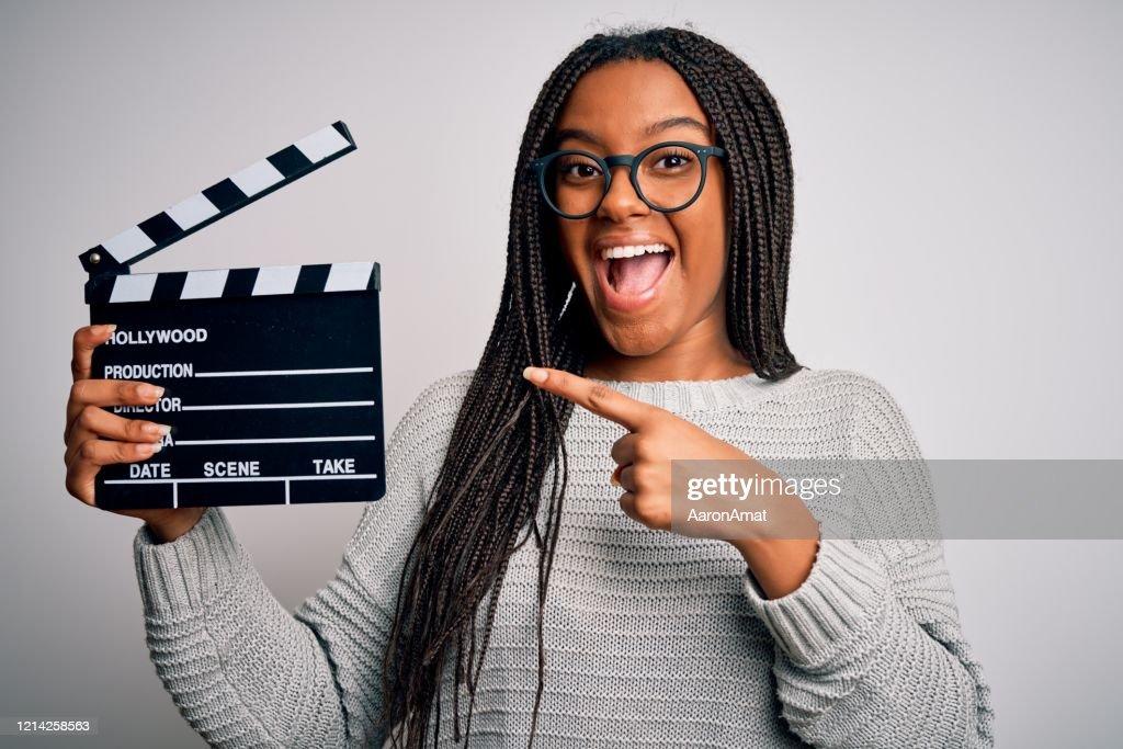 若いアフリカ系アメリカ人の監督の女の子は、手と指で非常に幸せな指を指す孤立した背景の上に拍手ボードを使用して映画を撮影 : ストックフォト