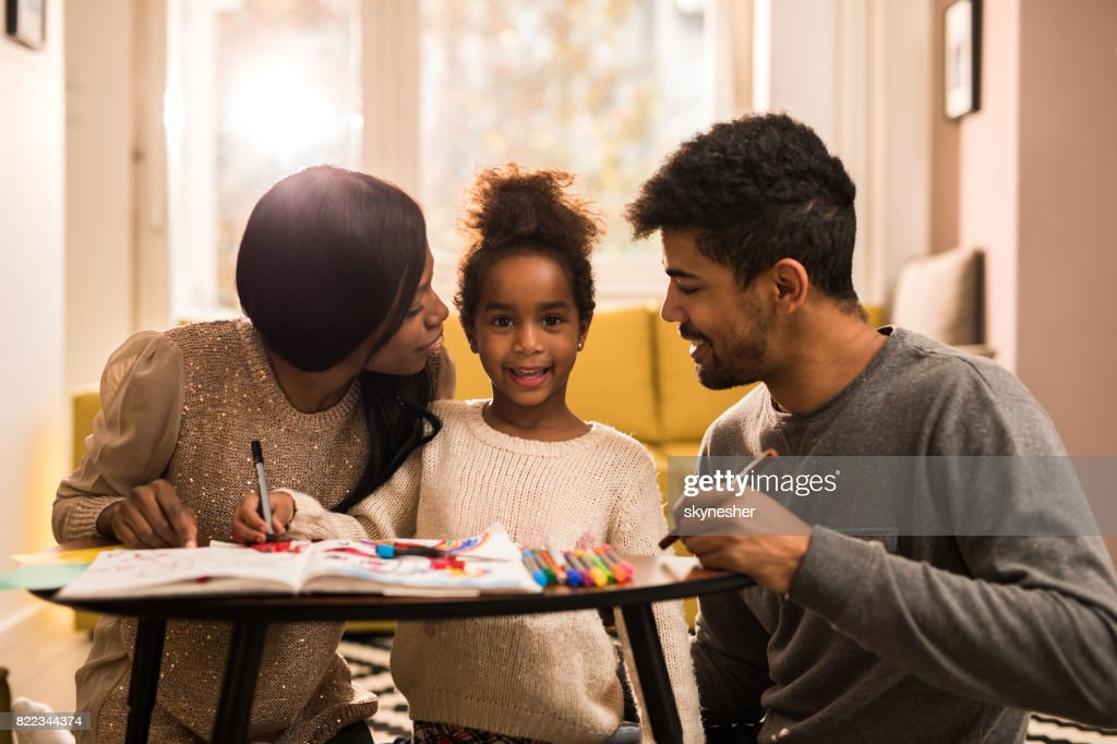 Young African American family drawing at home and enjoying in creative time together. : Stock Photo