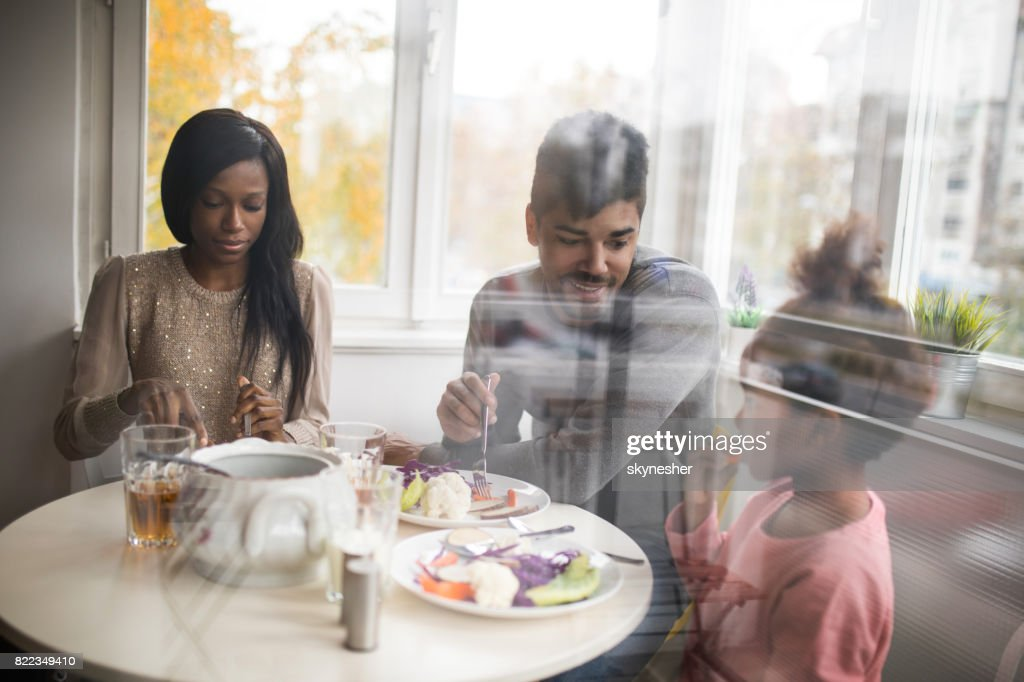 Young African American family having a lunch at home. : Stock Photo