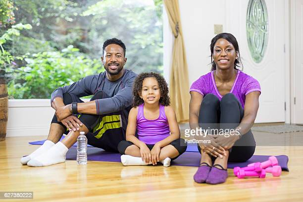Young African American family sitting in their daylight yoga studio