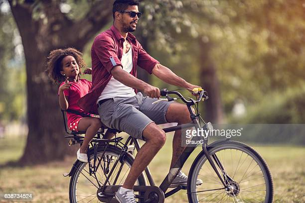 Young African American father and daughter on a bike outdoors.