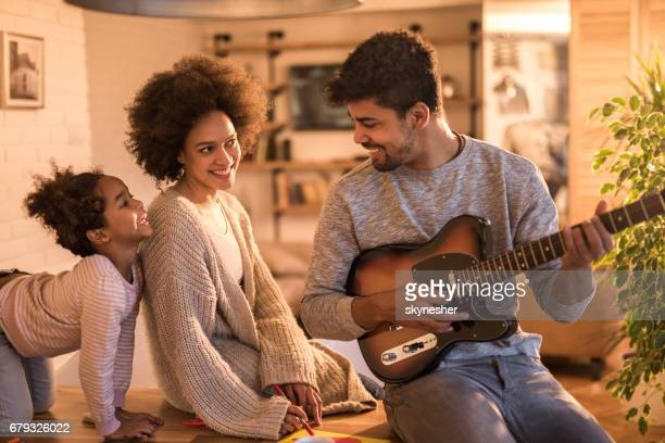 young african american father playing electric guitar to his family at home. - family at home stock photos and pictures