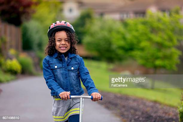 Young african american female riding a scooter