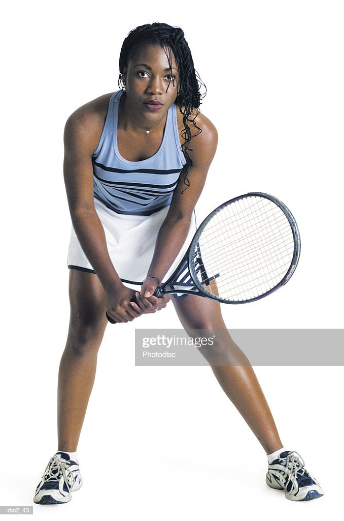 young african american female tennis player in blue tank top white skirt ready to return a serve : Foto de stock