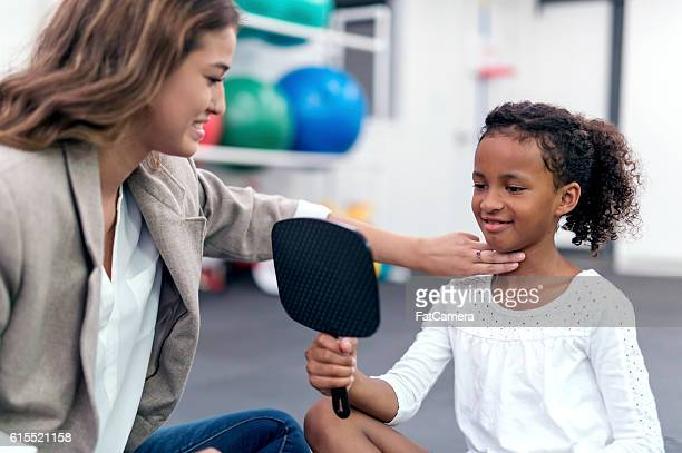 Young African American girl holding a mirror during a therapy exercise