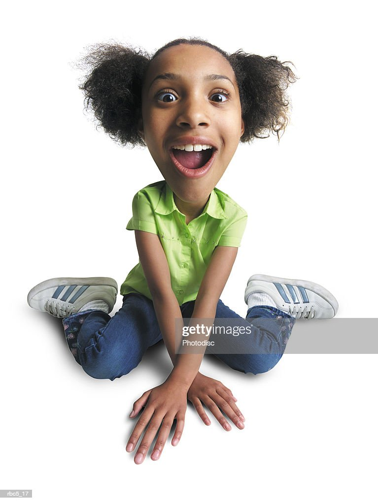 young african american girl sits on floor with hands crossed in front looks at camera with surprise : Stockfoto