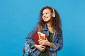 Young african american girl teen student in denim clothes, backpack headphones isolated on blue wall background studio portrait. Education in high school university college concept. Mock up copy space