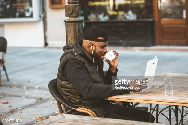 young african american is enjoying in coffee in the outdoor cafe - candid forum stock pictures, royalty-free photos & images