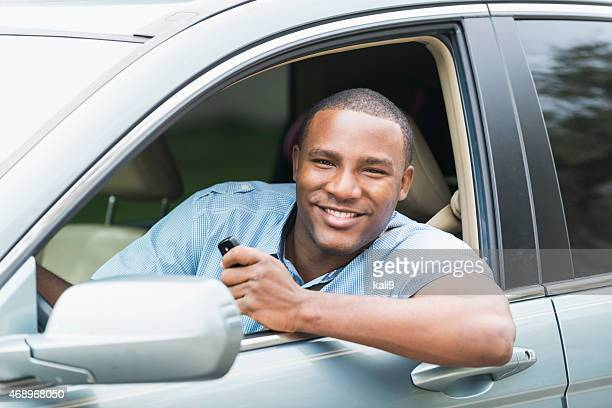 Young African American man driving car