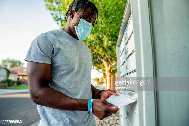 young african american man in his twenties wearing a covid-19 mask carrying a ballot to mail to vote in an election while social distancing - voting by mail stock pictures, royalty-free photos & images