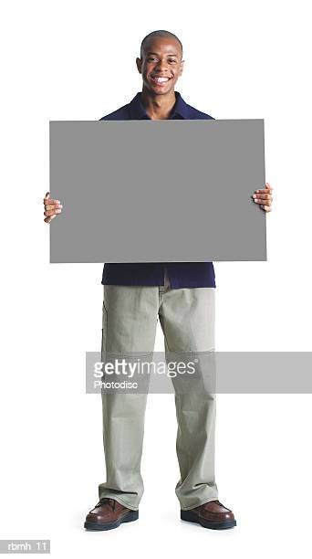 young african american man in tan pants black shirt holds blank sign in front of himself smiling