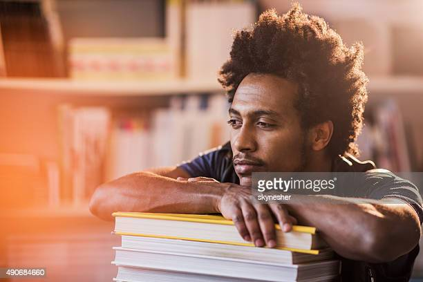 Young African American man relaxing on stack of books.