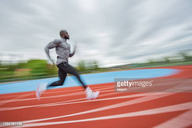 jovem afro-americano correndo em tartan. - sprint - fotografias e filmes do acervo