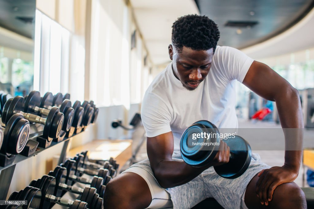 Young African American man sitting and lifting a dumbbell with the rack at gym : Stock Photo