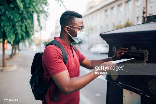 young african american man voting by mail - voting by mail stock pictures, royalty-free photos & images