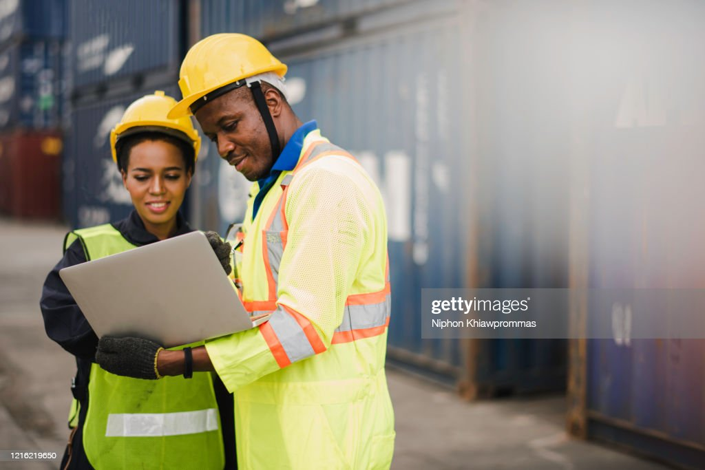Young African american men and woman worker Check and control loading freight Containers by use computer laptop at commercial shipping dock felling happy. Cargo freight ship import export concept : Stock Photo