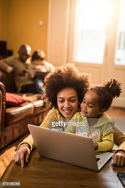 Young African American mother and daughter using laptop at home.