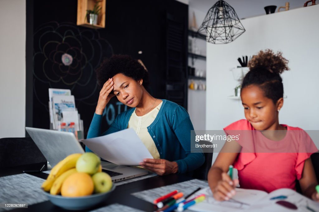 Young African American mother looking for a job using internet : Stock Photo