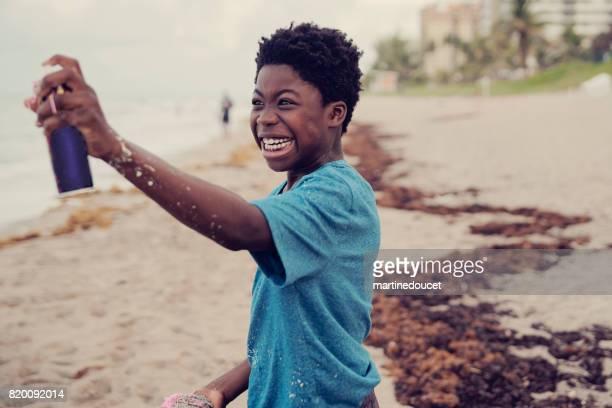 """jóvenes afroamericanos jugando con party string aerosol en la playa. - """"martine doucet"""" or martinedoucet fotografías e imágenes de stock"""