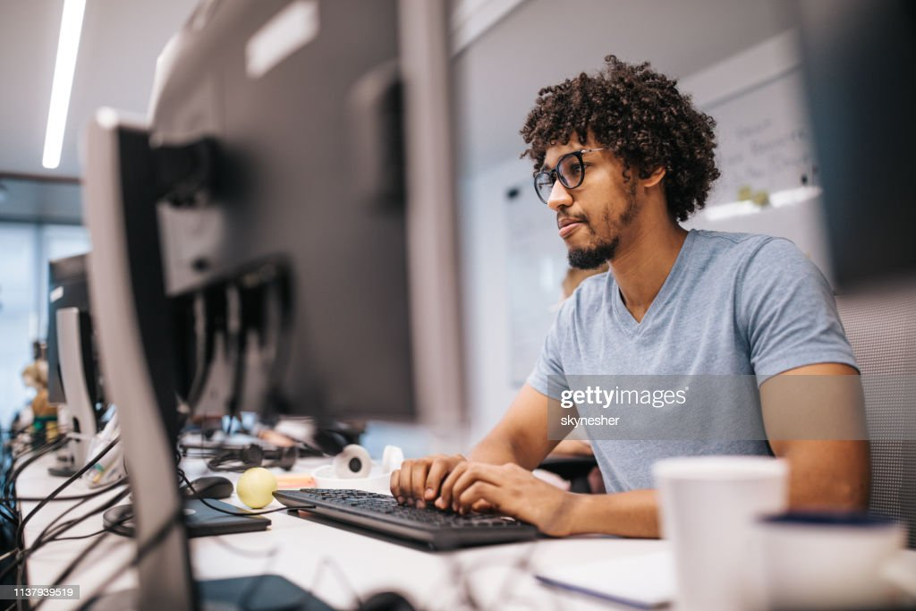 Young African American programmer working on desktop PC in the office. : Stock Photo